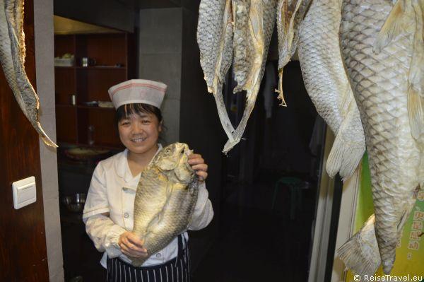 Köchin mit Fisch aus Qufu in China,